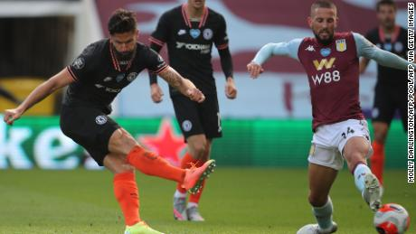 Chelsea's French striker Olivier Giroud scores his team's winning goal as his shot takes a deflection off the boot of the challenging Conor Hourihane to beat Orjan Nyland in the Aston Villa goal.