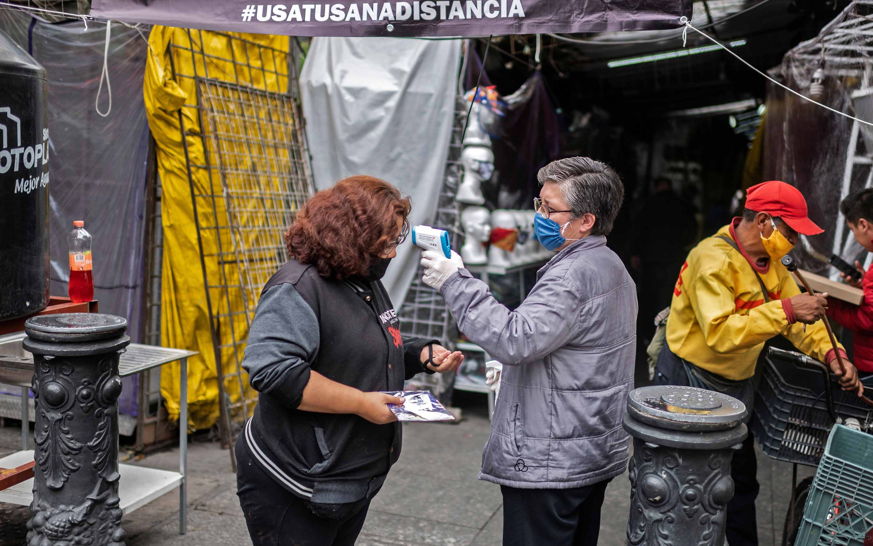 A woman has her temperature checked at Iztapalapa market, in Mexico City, on June 22.