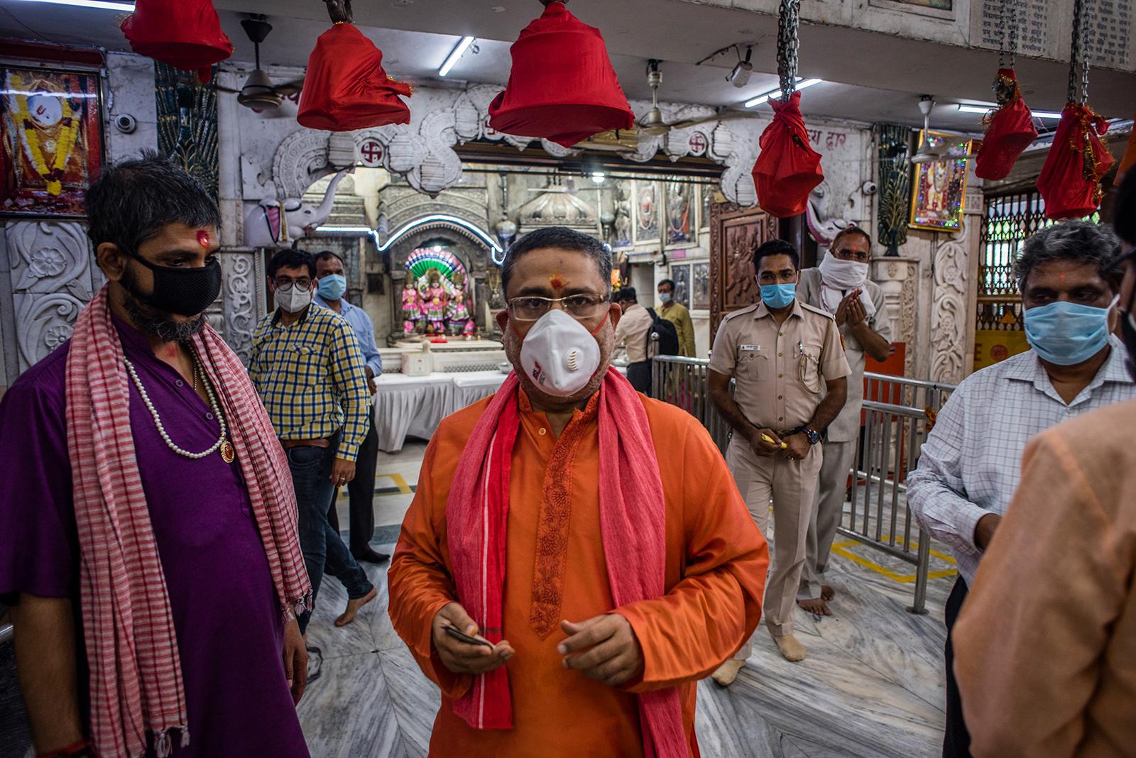 Indian Hindu priests and devotees walk inside Hunuman Mandir, on June 8, in Delhi.