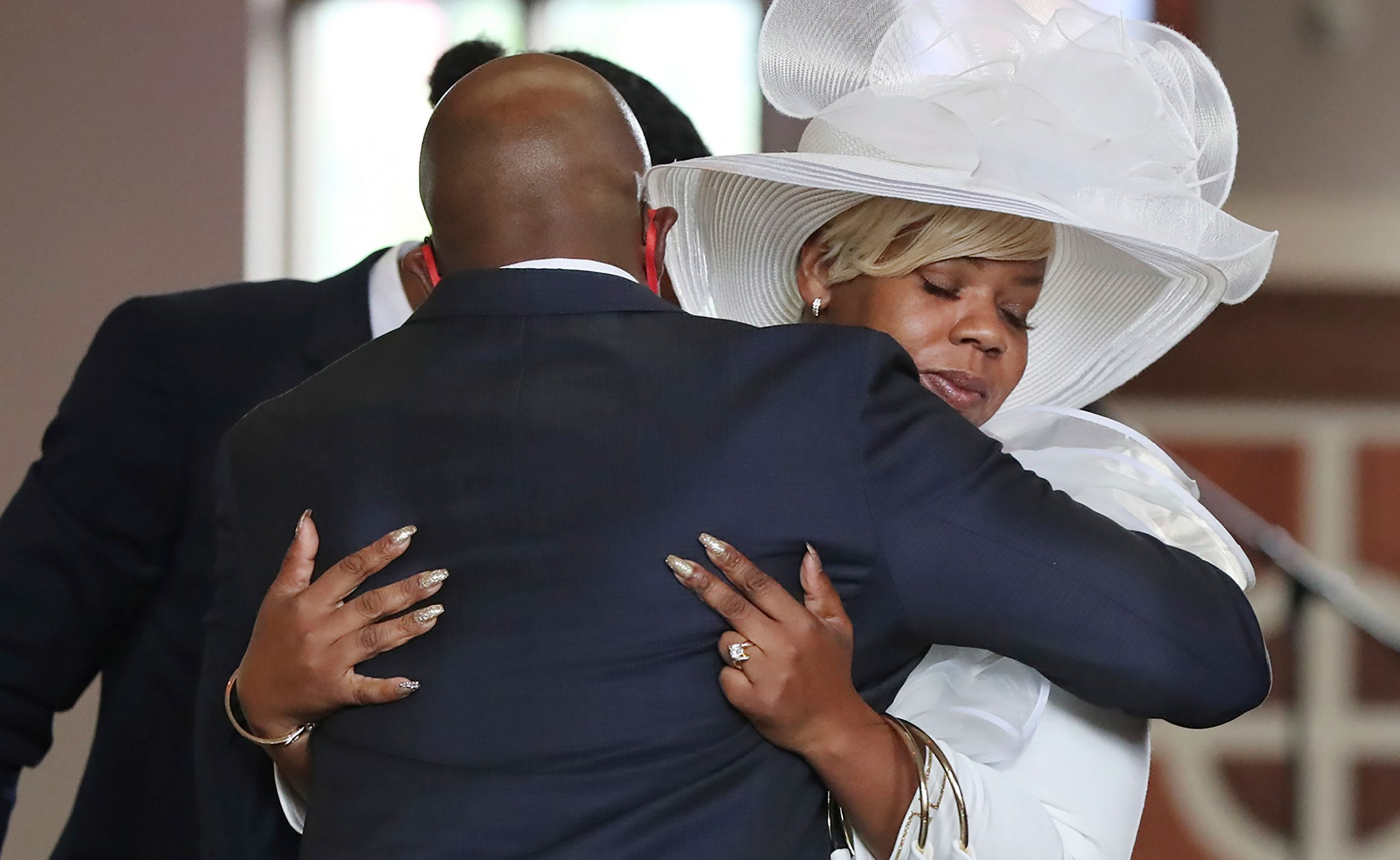 Rev. Raphael G. Warnock comforts Tomika Miller, the wife of Rayshard Brooks, during Brooks'  public viewing at Ebenezer Baptist Church on Monday, June 22 in Atlanta.