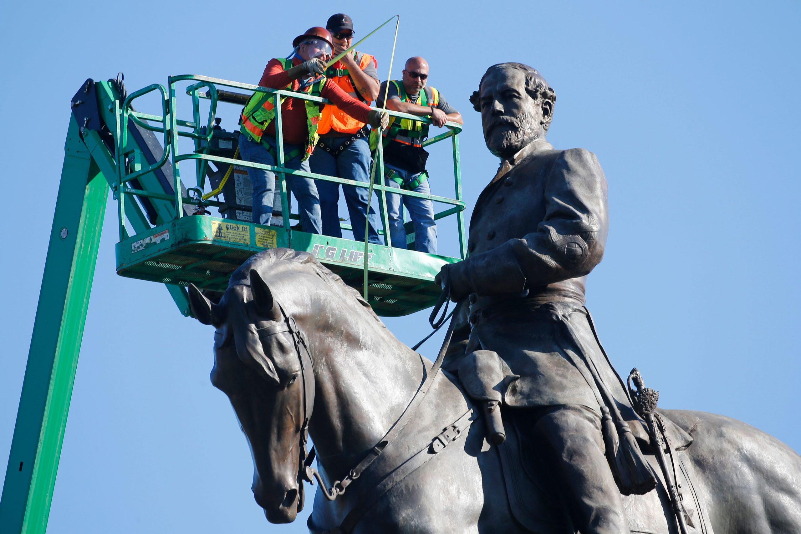 An inspection crew from the Virginia Department of General Services takes measurements of the Robert E. Lee statue in Richmond, Virginia, on June 8.