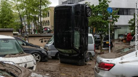 A car stands on its front after being upturned by flooding after the nearby Kuma River burst its banks, on July 5 in Hitoyoshi, Japan.