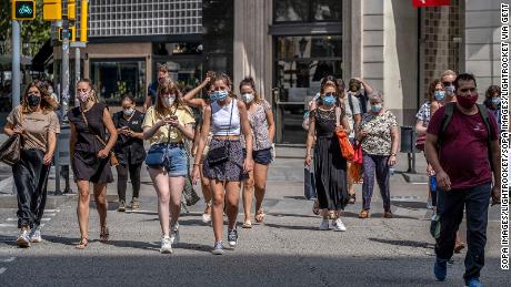People wear face masks in Barcelona, Spain, where those who don't do so in a public space face a 100 euro fine.