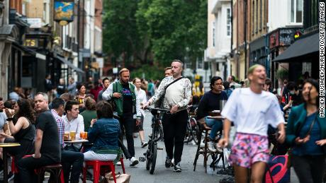 Customers enjoy their drinks in Soho, London, earlier in July as pubs, restaurants, hotels and hairdressers in England reopen.