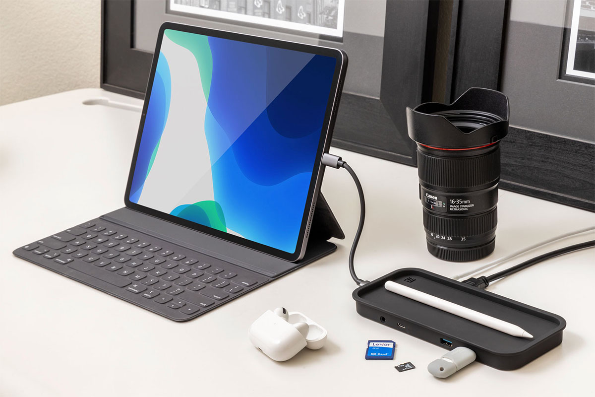 A desk, with a tablet charging and other tech accessories