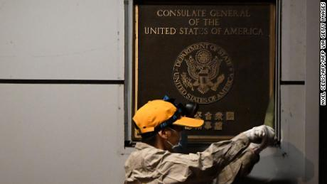 A worker attempts to remove a plaque on the wall outside the US Consulate in Chengdu, southwestern China.