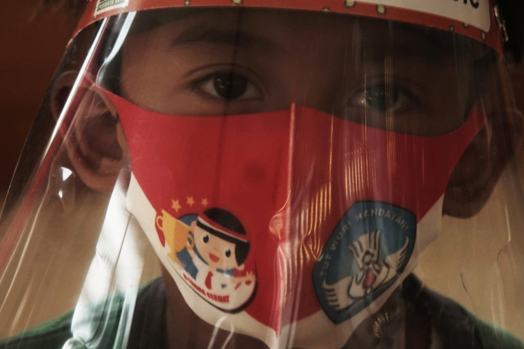 A pupil wearing a face shield and protective mask takes part on a face-to-face class session following the coronavirus disease (COVID-19) outbreak at a kindergarten in Semarang