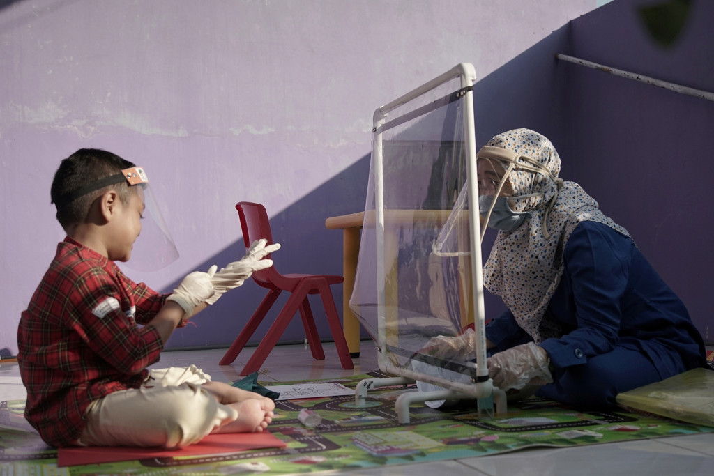 A teacher wearing a face shield and protective mask talks with her pupil through a plastic barrier as she visits her pupil at their house to evaluate their online class-session amid the coronavirus disease (COVID-19) outbreak in Semarang