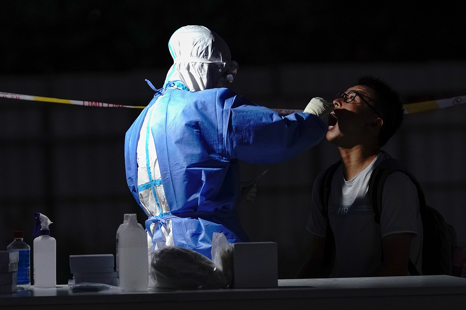 A medical worker wearing a protective suit takes a swab at a temporary test station on July 6, in Beijing.