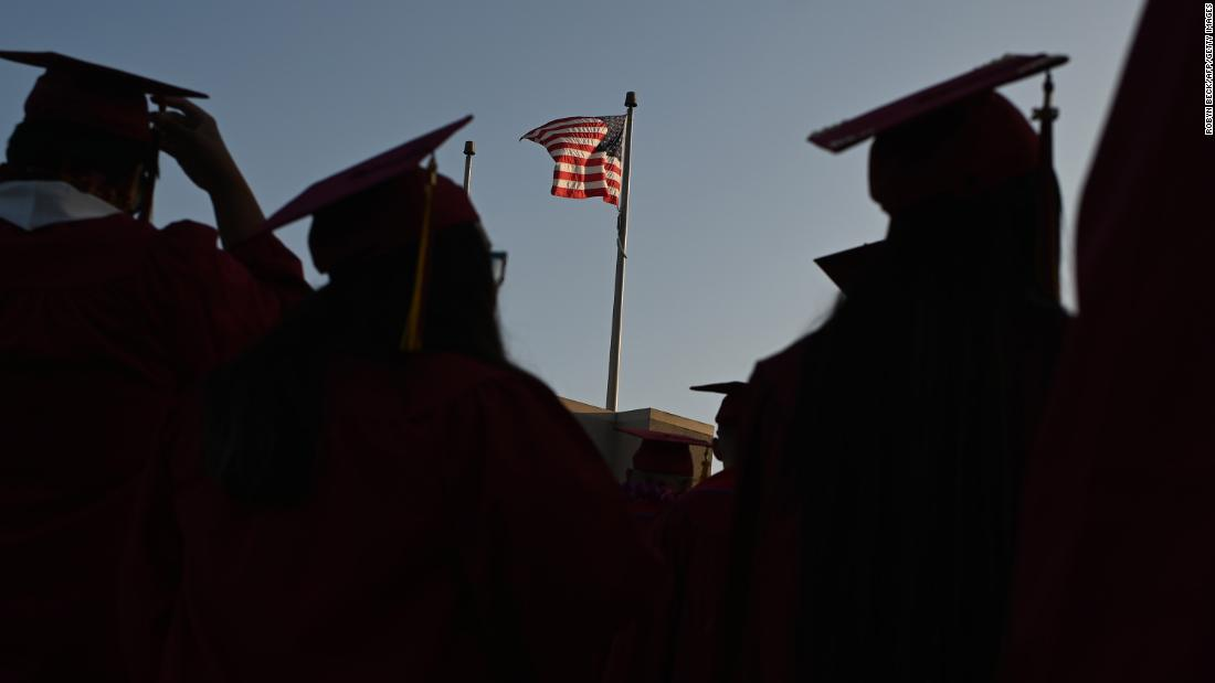 "A US flag flies above a building as students earning degrees at Pasadena City College participate in the graduation ceremony, June 14, 2019, in Pasadena, California. - With 45 million borrowers owing $1.5 trillion, the student debt crisis in the United States has exploded in recent years and has become a key electoral issue in the run-up to the 2020 presidential elections. ""Somebody who graduates from a public university this year is expected to have over $35,000 in student loan debt on average,"" said Cody Hounanian, program director of Student Debt Crisis, a California NGO that assists students and is fighting for reforms. (Photo by Robyn Beck / AFP) (Photo credit should read ROBYN BECK/AFP via Getty Images)"