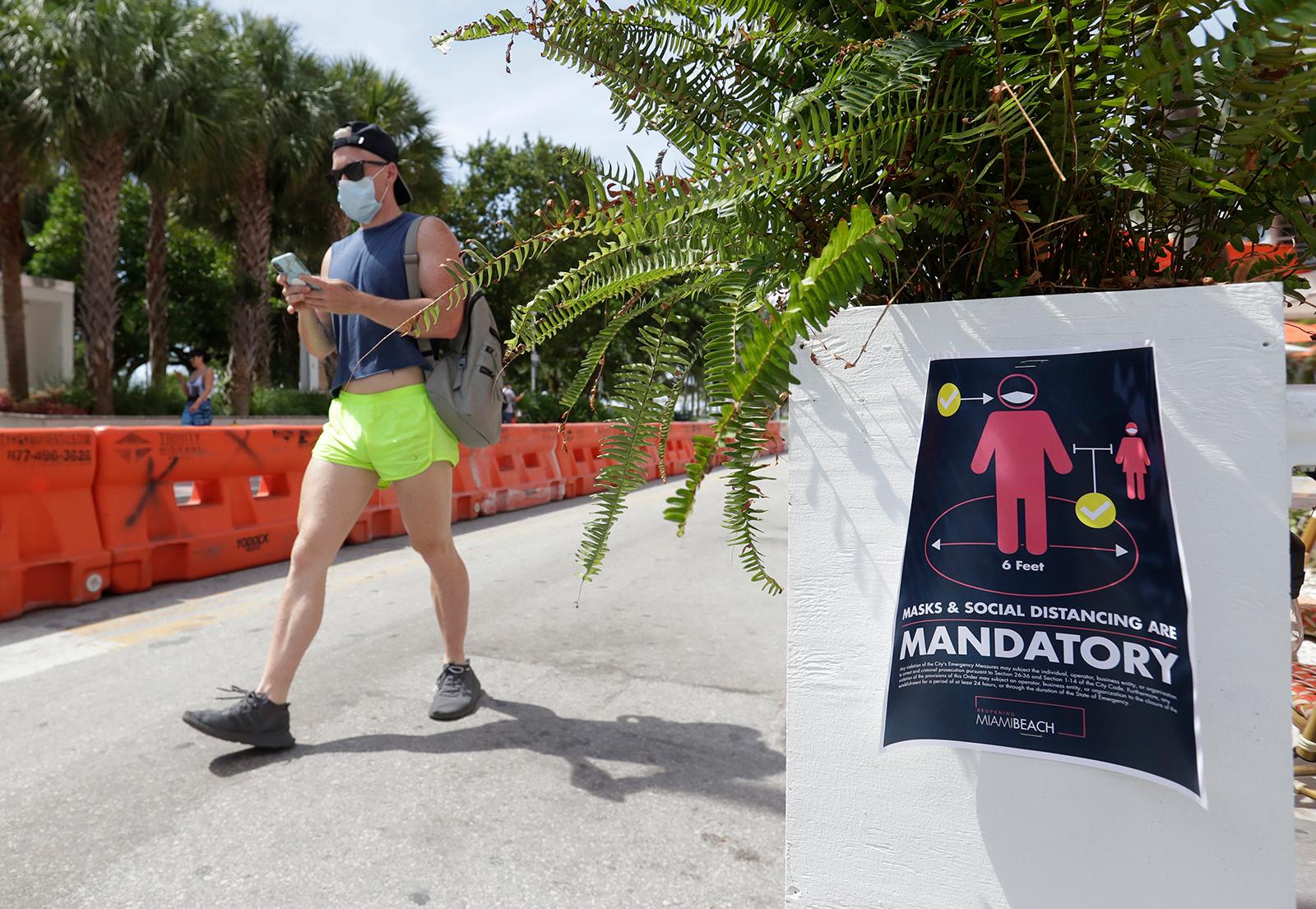 A pedestrian walks down Ocean Drive in Miami July 4.