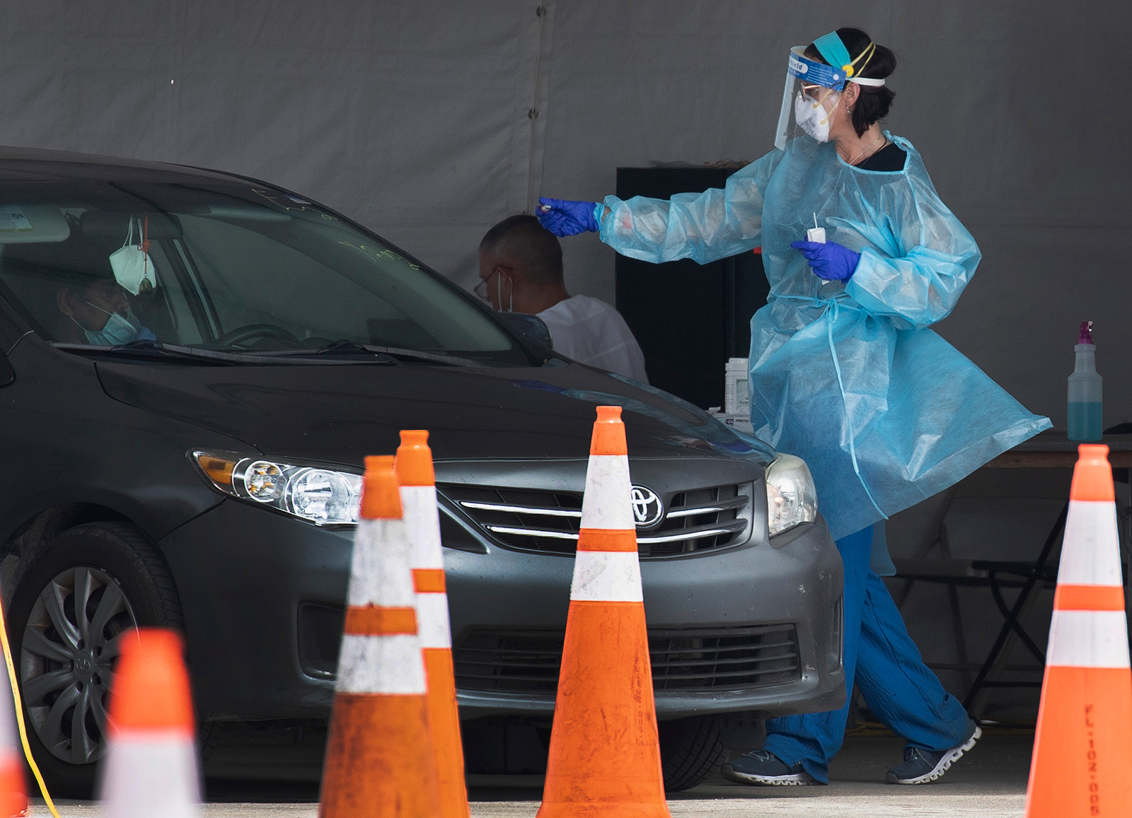 A healthcare worker tests a person for Covid-19 at the test site located in the Hard Rock Stadium parking lot on July 13, in Miami Gardens, Florida.