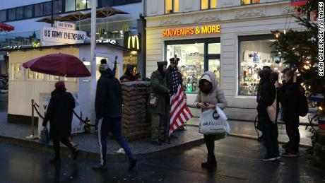 Tourists take photos of actors dressed as soldiers at former Checkpoint Charlie in Berlin, where US and Soviet tanks confronted each other in the early years of the Cold War.
