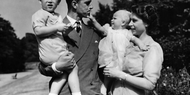FILE - In this Aug. 1951 file photo, Britain's Queen Elizabeth II, then Princess Elizabeth, stands with her husband Prince Philip, the Duke of Edinburgh, and their children Prince Charles and Princess Anne at Clarence House, the royal couple's London residence. (AP Photo/Eddie Worth, File)