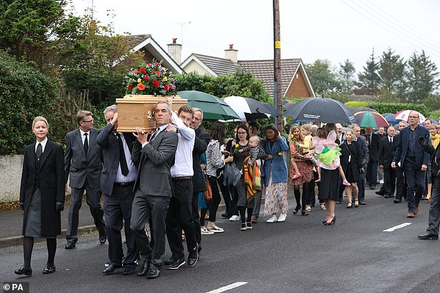 Nesbit carries his father's casket while mourners walk behind ahead of the funeral today.A song by Harry Connick Jr was played as the cortege passed mourners lining the burial route