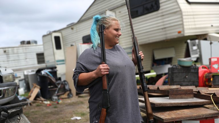 A woman emoves rifles from her home as she evacuates before the possible arrival of Hurricane Laura, in Cameron, Louisiana