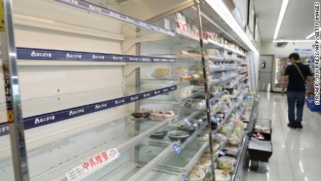 On September 6, a man shopped near empty food shelves at a convenience store in Hitoyoshi, Kumamoto Prefecture, as evacuation advice was issued due to Typhoon Hysh's approach.