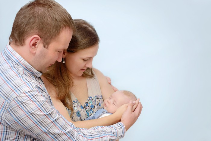 Couples holding a newborn baby in their arms.