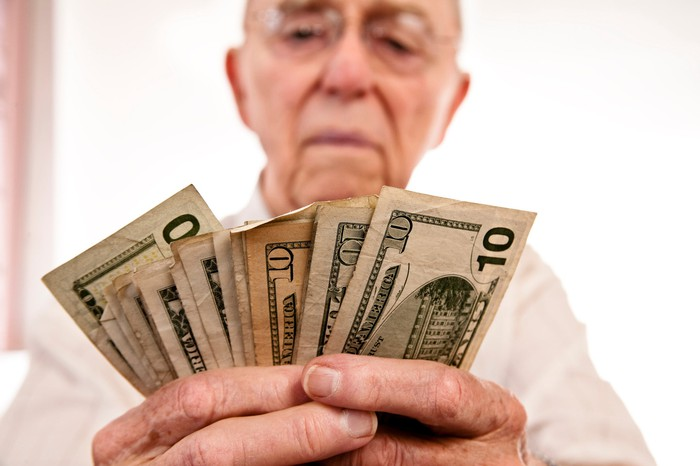 A senior counts the pile of money in their hand.