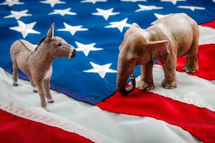 A Democrat donkey and a Republican elephant jump on top of the American flag.