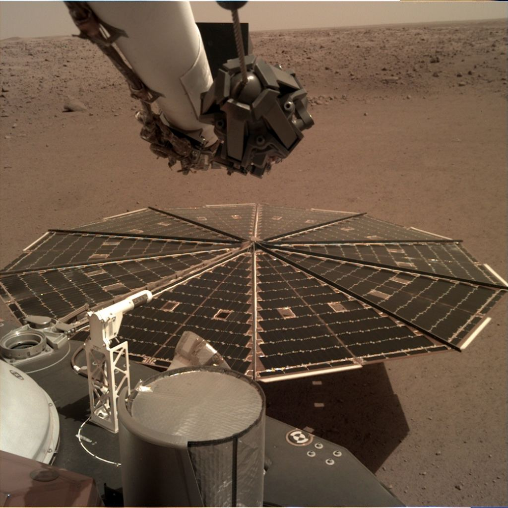 One of the 7-foot (2.2 m) wide solar panels on the Mars Insight was filmed by Lander's instrument deployment camera, which is attached to the elbow of the robotic arm.  The accumulated dust in the panels has reduced the power available to the mission.  Attribution: NASA / JPL-Caltech