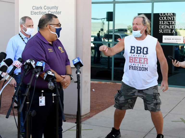 A protester interrupts a news conference by Clark County Registrar Joe Gloria (L) discussing ballot counting at the Clark County Election Department on November 4, 2020 in North Las Vegas, Nevada. Donald Trump and Joe Biden are in a tight race in the battleground state after yesterday's election.  (Photo by Ethan Miller/Getty Images)