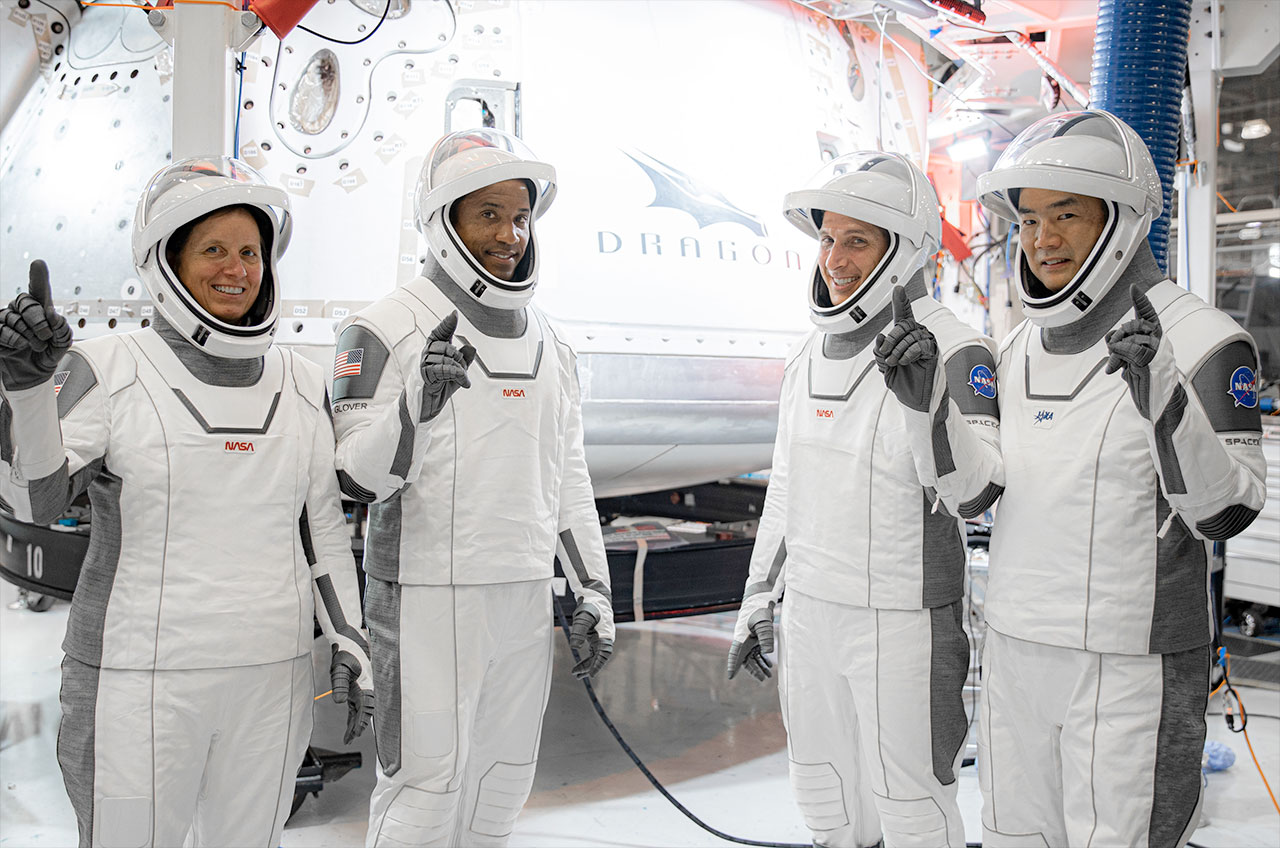 """SpaceX's Crew-1 astronauts pose in front of their Dragon capsule, including NASA astronauts Shannon Walker, Victor Glover, Michael Hopkins and Jaxa astronaut Sochi Noguchi. """"Defense,"""" Headquartered in SpaceX, Hawthorne, California."""