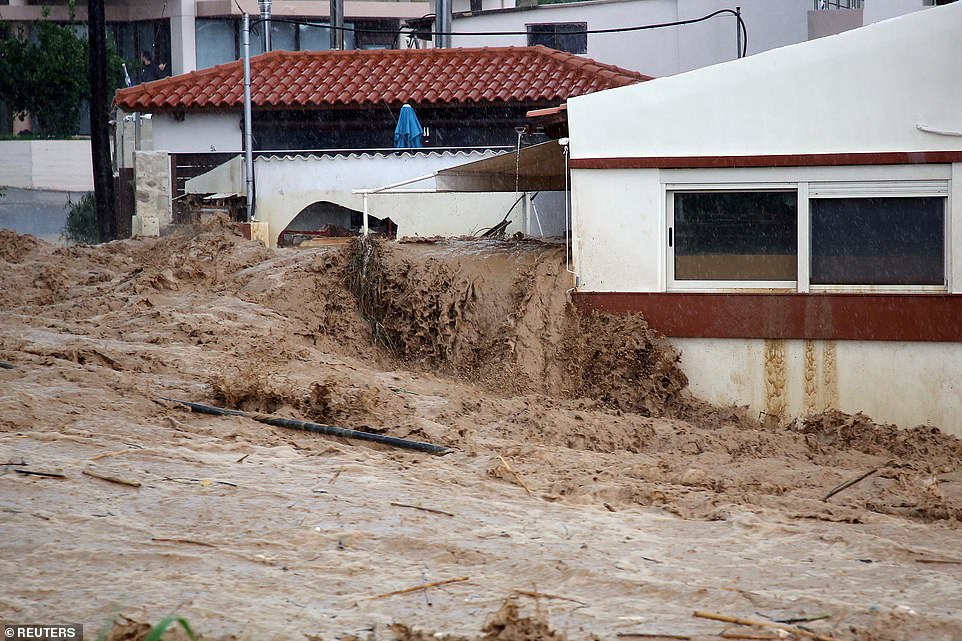 Flooding emerges from a building during heavy rains in the village of Gornus