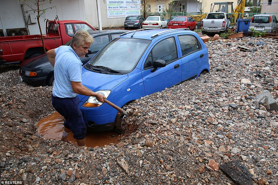 An area in Crete seeks to clear rocks and mud around parked cars following the devastating floods on the Greek island.