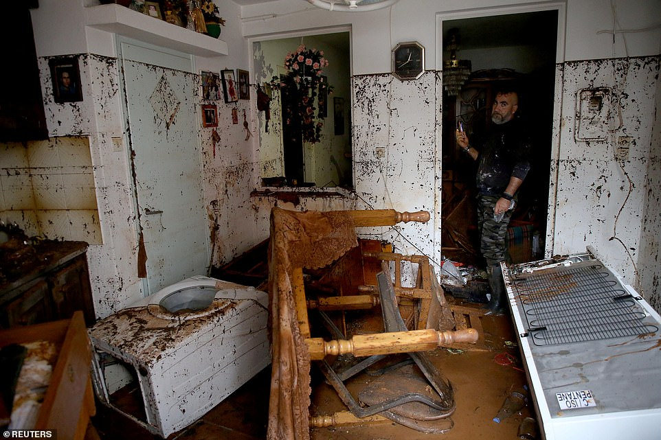 A local was standing inside the damaged house, where tables and kitchen utensils were submerged in the floodwaters inside his property.