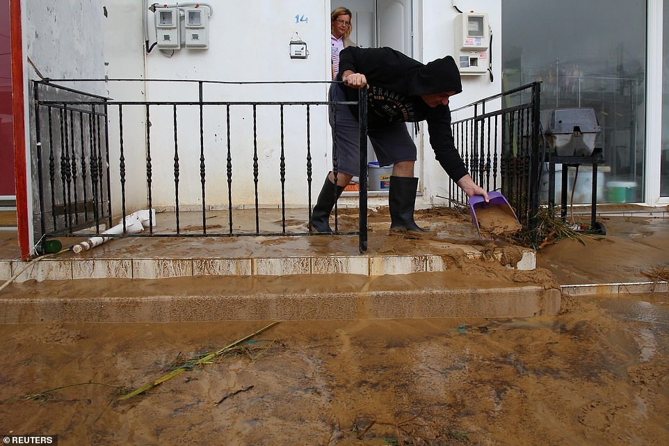 A local man removes sludge and debris from his balcony following the deposition of sludge from rivers flowing into towns and villages.
