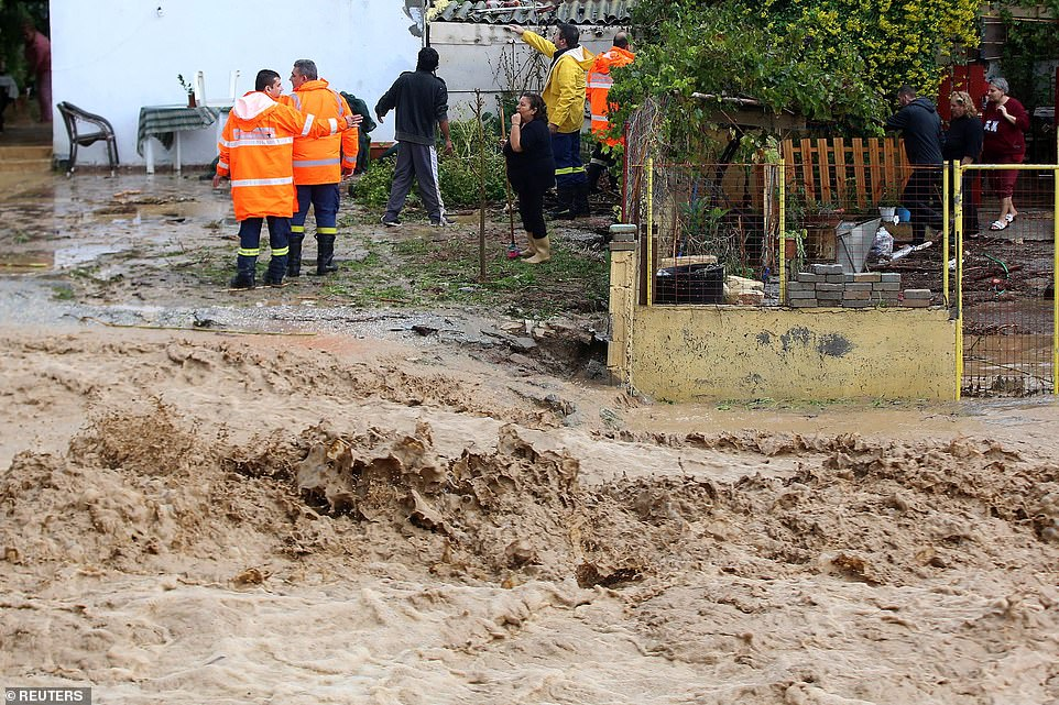 Locals and firefighters stand near the threat of flooding destroying everything on the tourist island's path