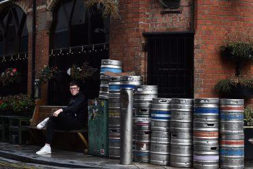 A customer is seen sitting outside Bittles bar beside beer kegs in Belfast city centre on October 14, 2020 in Belfast, Northern Ireland.