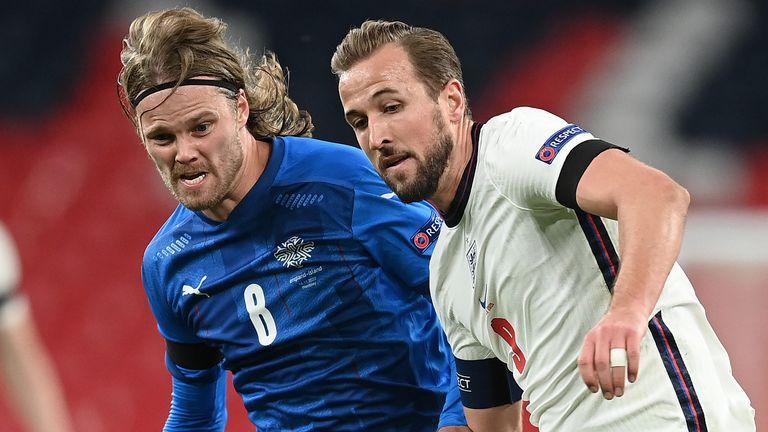 Birkir Jarnason of Iceland and Harry Kane of England fight for possession