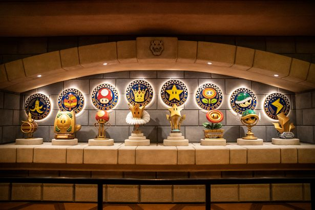 A row of trophies from Mario Kart at the new Bowser Castle attraction
