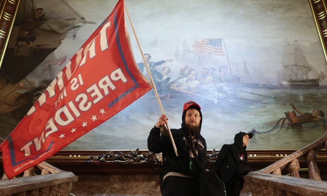 A protester holds a flag in support of President Trump inside the U.S. Capitol building near the Senate Chamber Photo: Win MCNM / AFP