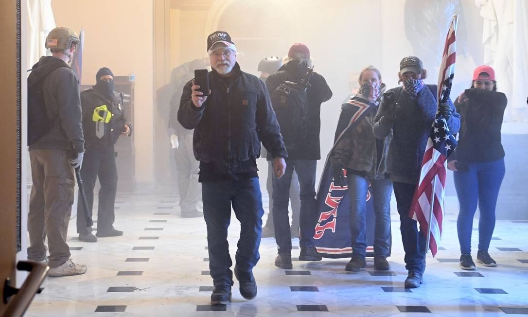 Supporters of President Donald Trump enter the capital as the corridor of the building picks up tear gas Photo: SAUL LOEB / AFP