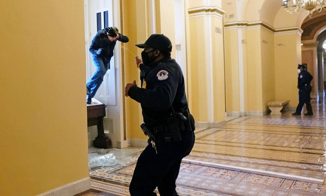 Capital police officer throws pepper spray at a protester trying to enter a Congress building Photo: POOL / REUTERS