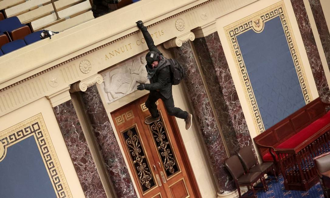 A protester is seen hanging in the Senate Pelnary Hall Photo: WIN MCNAMEE / AFP