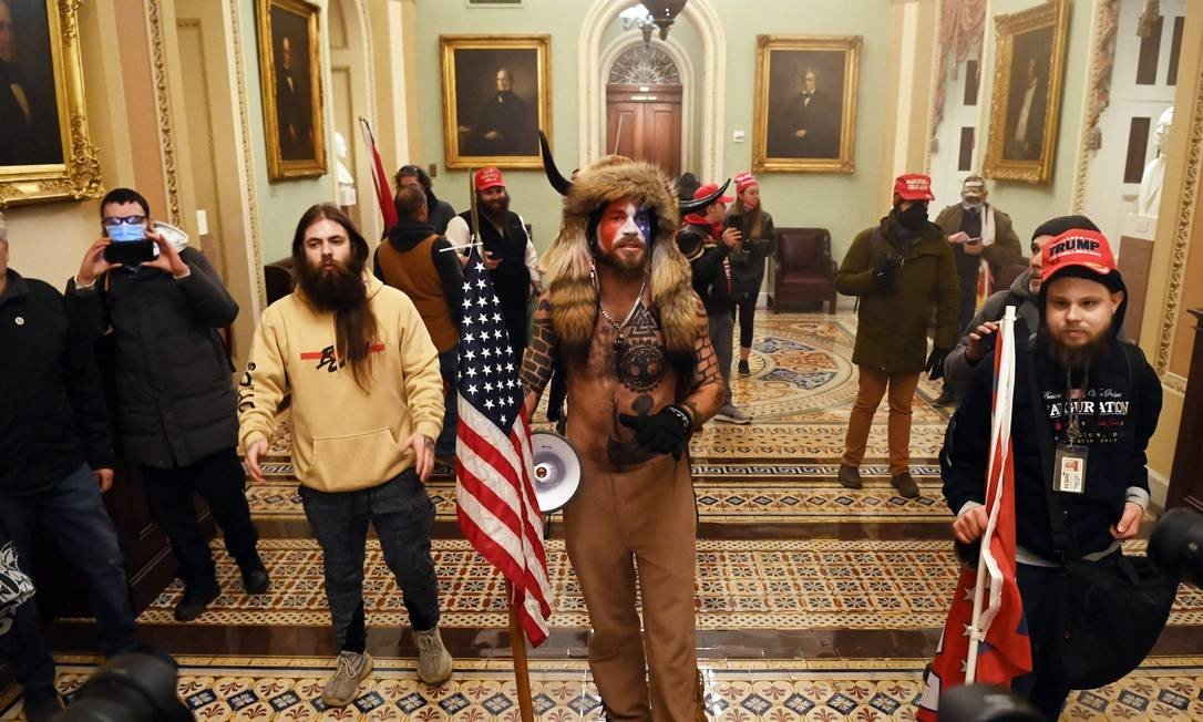 Jake Angeli wore animal skins and horned hats during a protest on Wednesday, and his face painted in the colors of the United States flag Photo: SAUL LOEB / AFP