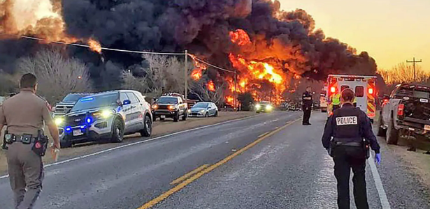 A train carrying gasoline collides with a truck, causing an explosion
