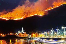 Uma enorme fogueira de tojo atravessa as Montanhas Mourne em Co Down, vista de Newcastle