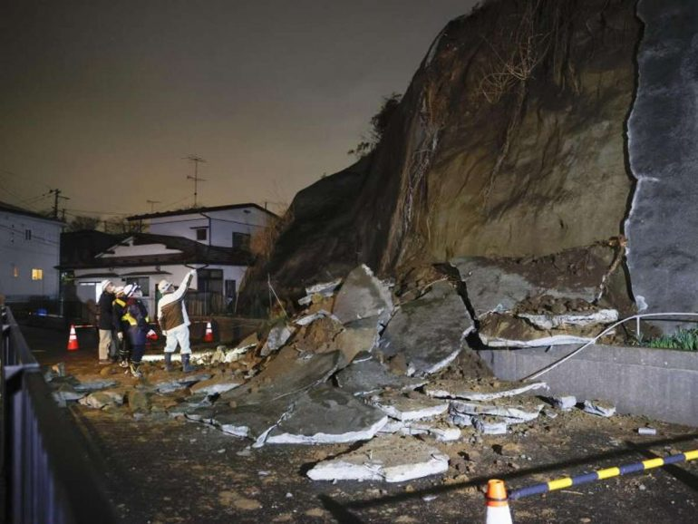 Menschen stehen vor eingestürzten Teilen einer Klippe. Eine Tsunami-Warnung in Folge eines starken Erdbebens im Nordosten Japans ist wieder aufgehoben worden. Foto: ---/Kyodo/dpa