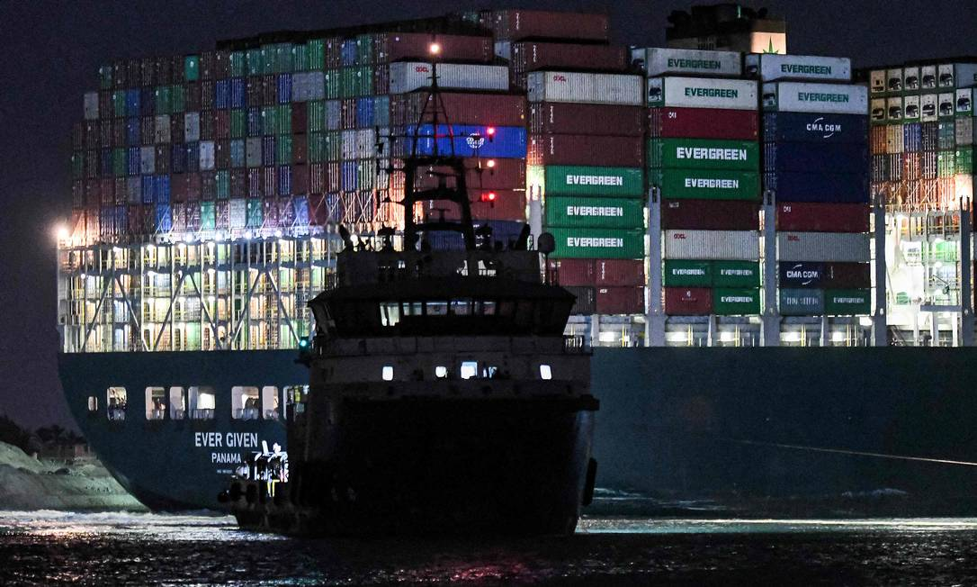 Tug works overnight to unpack a giant cargo ship Photo: AHMED HASAN / AFP
