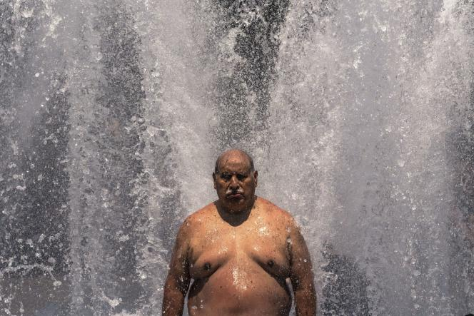 On June 27, 2021, a man cools down in a fountain in Portland, Oregon.