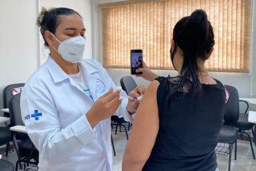 Mulher tira selfie enquanto é vacinada
