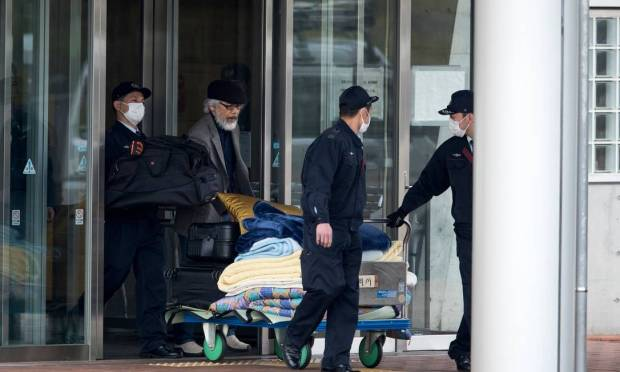 Takashi Takano, one of Carlos Ghose's lawyers, and security guards smuggle personal belongings before the release of the former Nissan executive Photo: Behroos Mehri / AFP