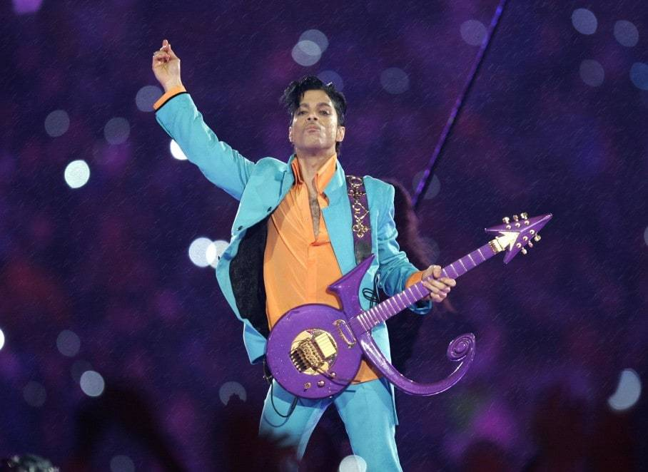 Singer Prince at Super Bowl Half Time Show playing guitar in the shape of his name