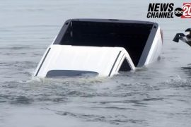 The pickup truck sinks into the lake during a live news link