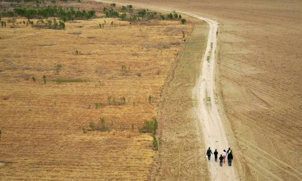 Immigrant families seeking refuge from Honduras and Guatemala walked through a dirt road after illegally crossing the Rio Grande from Mexico to the United States in Penitas, Texas.